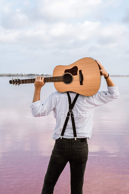 From behind man in white shirt holding acoustic guitar behind back while standing on shore on cloudy weather in USA — Foto stock