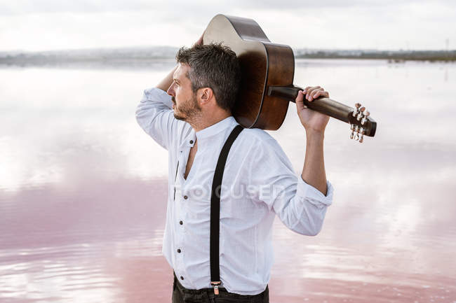Homem de camisa branca segurando guitarra acústica enquanto estava em pé na costa durante o dia nublado enquanto olhava para longe — Fotografia de Stock