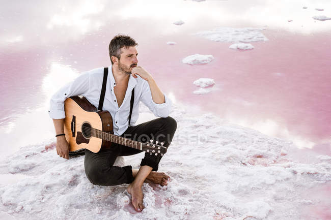 Wistful man with acoustic guitar sitting on beach looking away surrounded with smooth sea reflecting majestic cloudscape — Foto stock