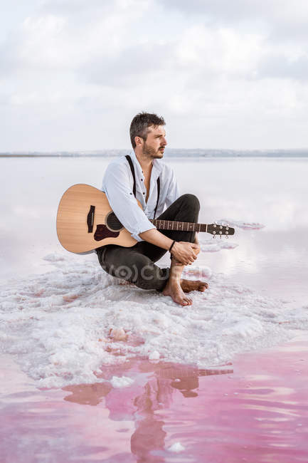 Wistful man with acoustic guitar sitting on beach looking away surrounded with smooth sea reflecting majestic cloudscape — Stock Photo