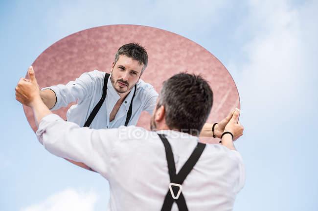 Reflexión de bajo ángulo del hombre penoso en camisa y suspensores que se levantan sobre el cielo azul y el espejo ovalado. - foto de stock