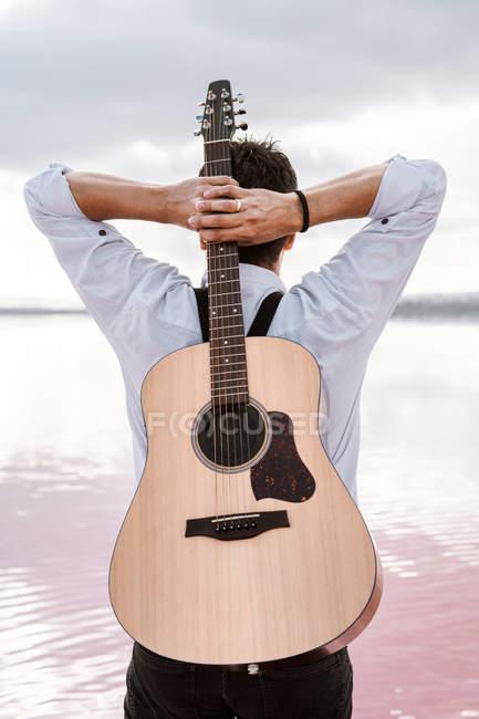 De trás do homem em camisa branca segurando guitarra acústica atrás de trás enquanto estava na costa em tempo nublado — Fotografia de Stock