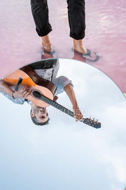 Desde arriba el reflejo del hombre tocando guitarra mientras estaba de pie en el agua por la costa sobre el cielo azul en el espejo ovalado. - foto de stock