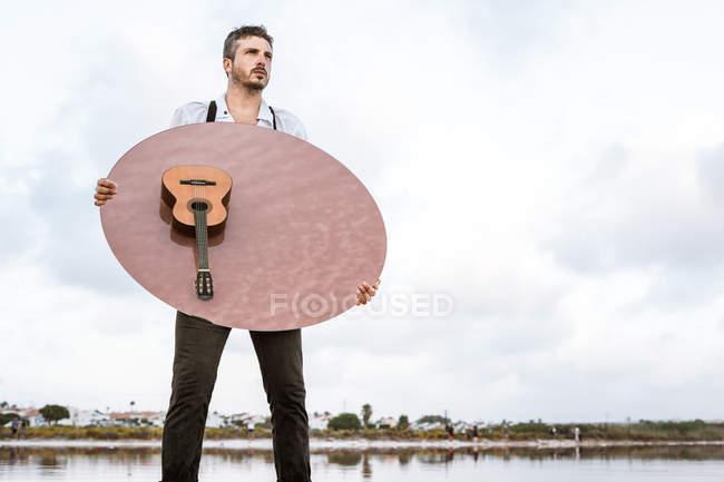 Hombre que sostiene espejo oval con reflejo de guitarra en agua rosa - foto de stock
