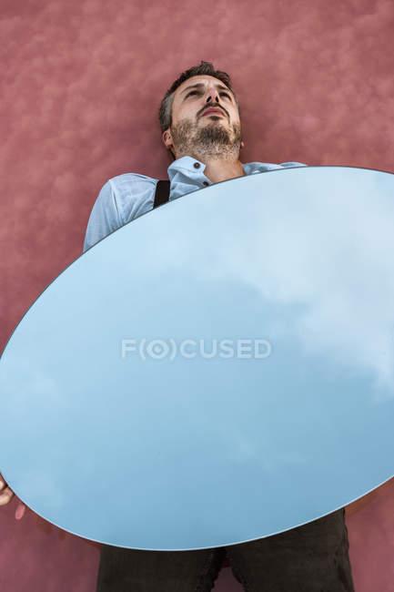 De arriba penoso hombre acostado sobre el agua rosada que sostiene el espejo ovalado que refleja el cielo azul. - foto de stock