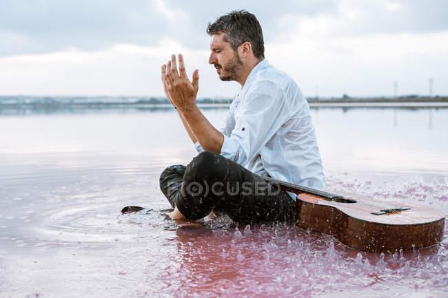 Homme en chemise blanche et bretelles jetant de l'eau au visage assis sur la plage avec de l'eau rose près de la guitare acoustique — Photo de stock