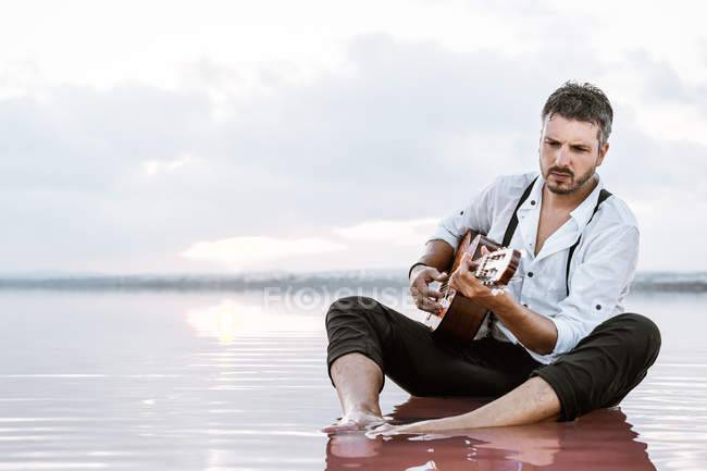 Wistful man playing acoustic guitar sitting on beach surrounded with smooth sea reflecting majestic cloudscape — Stock Photo