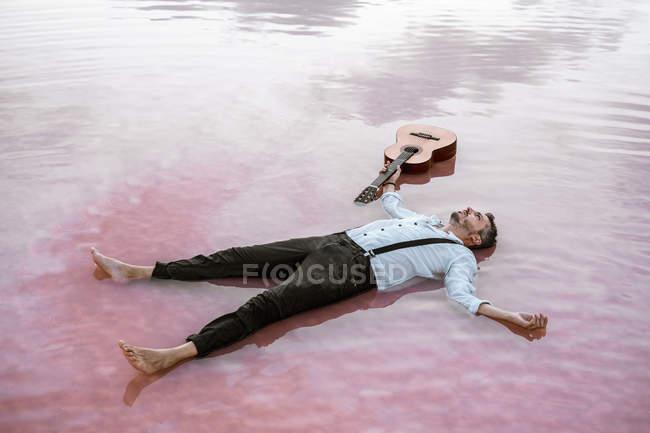Сверху человек в белой рубашке и подтяжках, лежащих на спине, глядя в сторону и плавая с акустической гитарой в море на песчаном берегу — стоковое фото