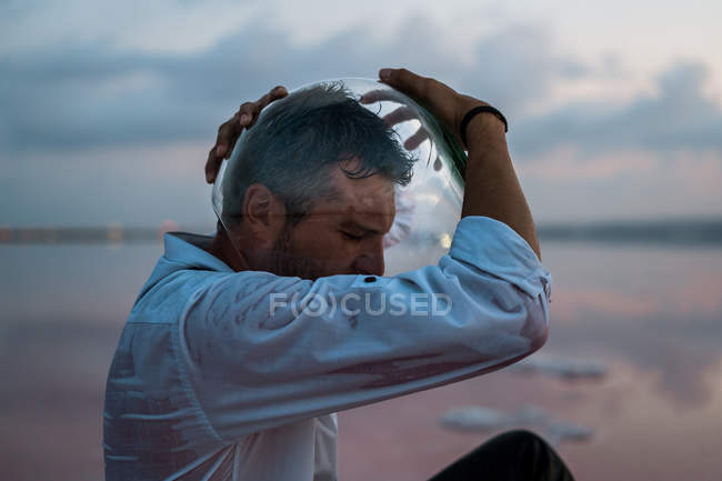 Pensive man in wet shirt taking out empty aquarium while sitting still by the seaside in twilight — Stock Photo