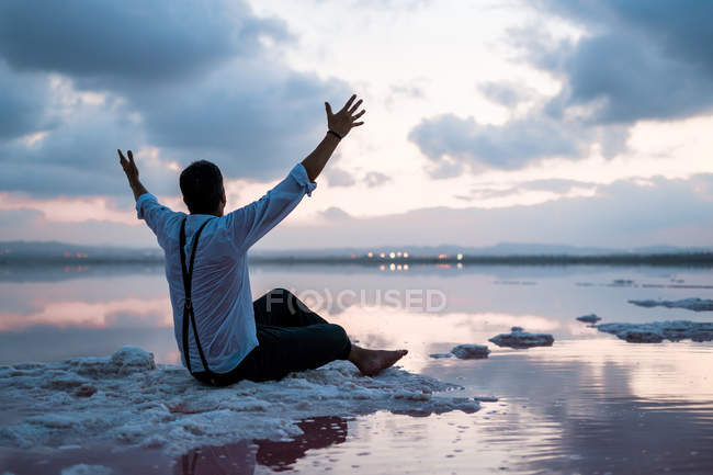 From behind man in wet clothes gazing and sitting with outstretched arms at coast in cloudy sunset — Stock Photo