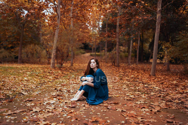 Charming sad woman in blue dress sitting on alley strewn with leaves in autumn park with trees in orange red brown foliage — Stock Photo
