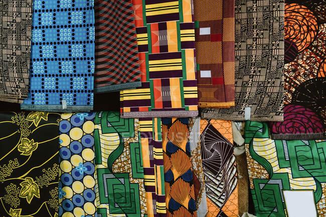 Bouquet de tissu brillant accroché à la corde en magasin sur le marché de rue en Gambie — Photo de stock