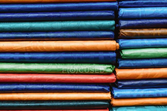 Pilhas de tecido multicolorido brilhante colocado na prateleira na loja no mercado de rua na Gâmbia — Fotografia de Stock