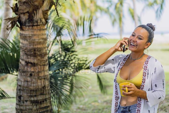 Femme heureuse parlant sur smartphone regardant loin tout en tenant une tasse et debout sur une pelouse ensoleillée près d'un palmier au Costa Rica — Photo de stock