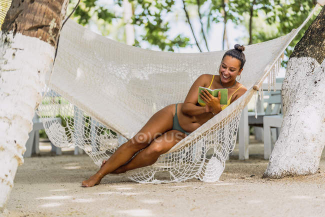 Delighted woman in swimsuit sitting using mobile phone in hammock at exotic seaside in Costa Rica — Stock Photo