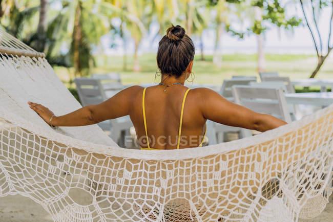 Vista posteriore della donna in costume da bagno seduta in amaca al mare esotico in Costa Rica — Foto stock