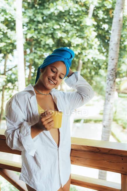 Contenu femme dans l'enveloppe de la tête dégustant une boisson chaude tout en restant debout sur une rambarde en bois et regardant les arbres feuillus au Costa Rica — Photo de stock