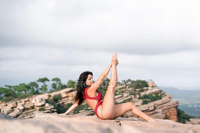 Vista lateral de la mujer descalzo con traje de baño rojo sentado sobre rocas y piernas estiradoras mientras se prepara para bailar. - foto de stock