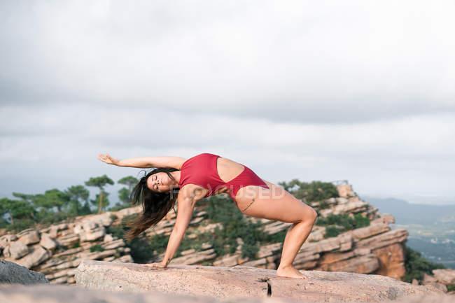 Полная длина босиком женщина в красном купальнике опираясь на камни во время танцев на вершине скал против пасмурного неба в природе — стоковое фото
