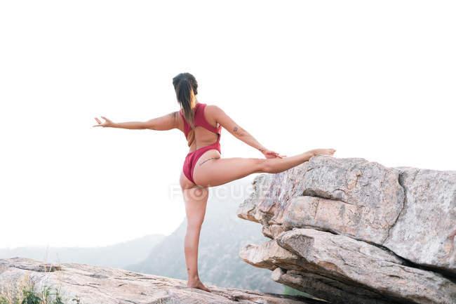 Vista trasera de dama con traje de baño rojo que mantiene la pierna en las rocas y estira el brazo mientras baila con un clima nebuloso en la naturaleza. - foto de stock
