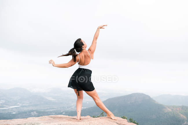 Back view of elegant barefoot lady in white top and black skirt raising arm and dancing on stones on misty weather in nature — Stock Photo