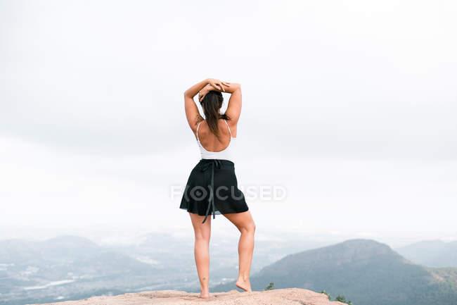 Visão traseira da mulher irreconhecível em pé sobre rochas e contemplando paisagem montanhosa em tempo nublado no campo — Fotografia de Stock