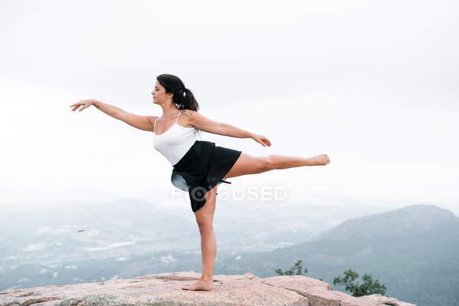Danza femenina con los ojos cerrados equilibrando la pierna mientras baila sobre rocas en un clima nebuloso en la naturaleza. - foto de stock