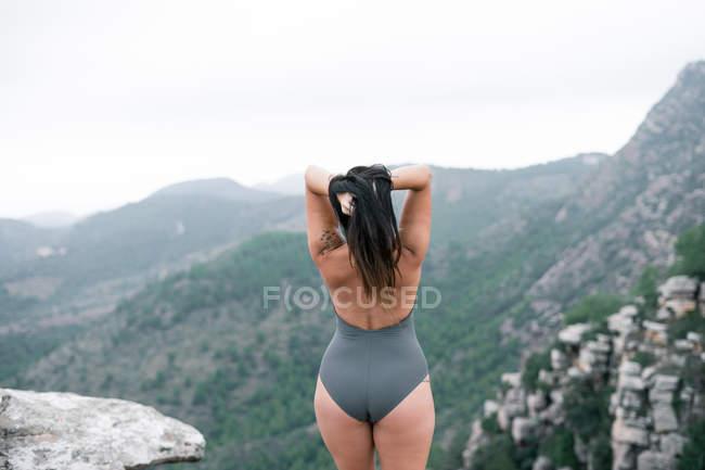 Vista posteriore di donna irriconoscibile in costume da bagno in piedi su rocce contemplando paesaggio montano su tempo nuvoloso — Foto stock