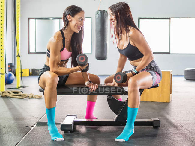 Happy sportswomen training with dumbbells in modern gym — Stock Photo