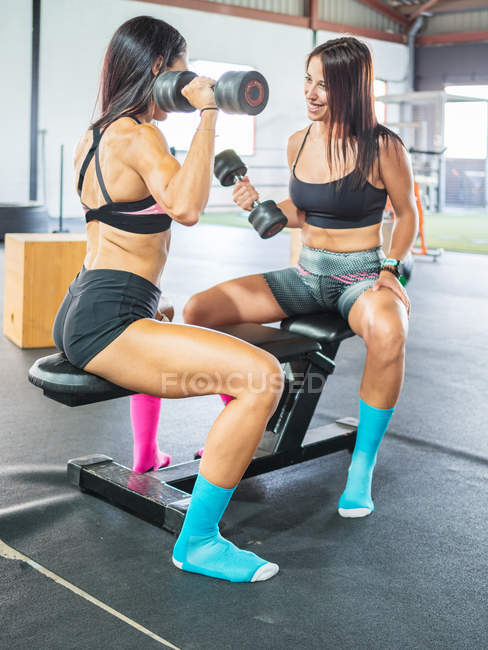 Joyful athletes in sportswear working out with weights while sitting on fitness bench in professional gym — Stock Photo