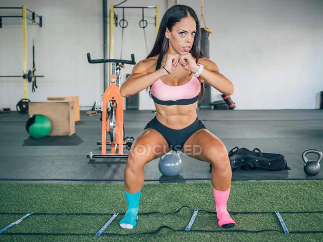Athlète très confiant en tenue de sport faisant de l'exercice de squat avec les bras fléchis et regardant à huis clos au gymnase. — Photo de stock