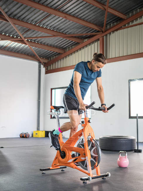 Sportsman exercising on stationary bicycle in modern gym — Stock Photo