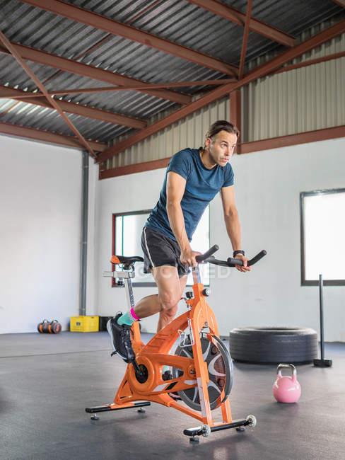 Дорослі спортсмени спортивного одягу зосереджують увагу на велосипеді в спортивному клубі вдень. — стокове фото