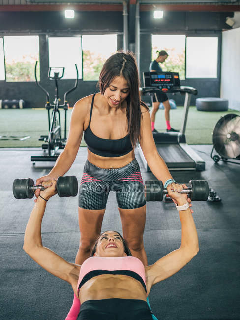 Smiling fit woman in sportswear insuring strong female partner lying on fitness bench and working out with weights — Stock Photo