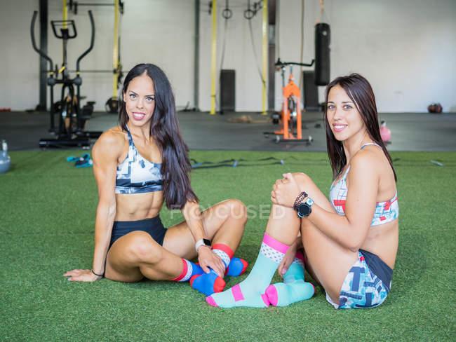 Смолящие спортсмены в спортивных костюмах сидят со скрещенными ногами на зеленом ковре и смотрят в камеру в тренажерном зале — стоковое фото