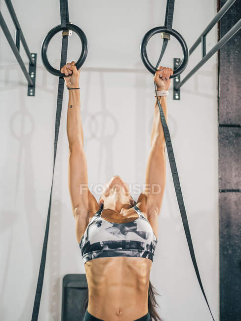 Strong female athlete in gray sportswear working out on black gymnastic rings against white wall in sport club — Stock Photo