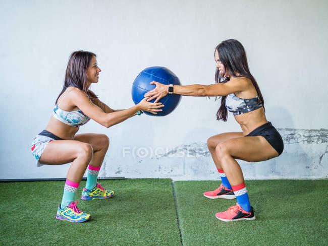 Веселые женщины тренируются с мячом в современном спортзале — стоковое фото