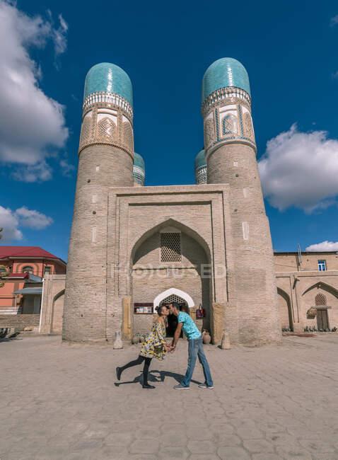 Seitenansicht ethnischer Männer und Frauen, die sich Händchen halten und küssen, während sie vor einem traditionellen islamischen Gebäude in Buchara, Usbekistan stehen — Stockfoto