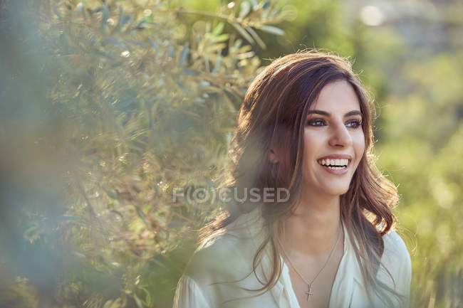 Graceful stylish beautiful young woman in green garden looking away with smiling — Stock Photo