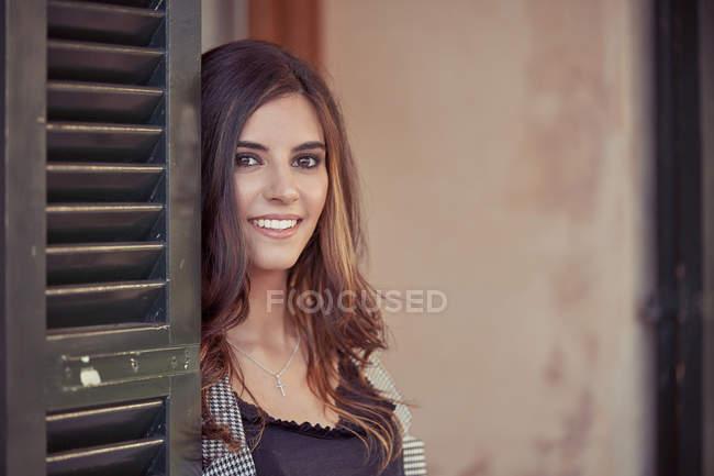 Affascinante donna d'affari con acconciatura riccia guardando la fotocamera e sorridente in piedi vicino alla porta — Foto stock