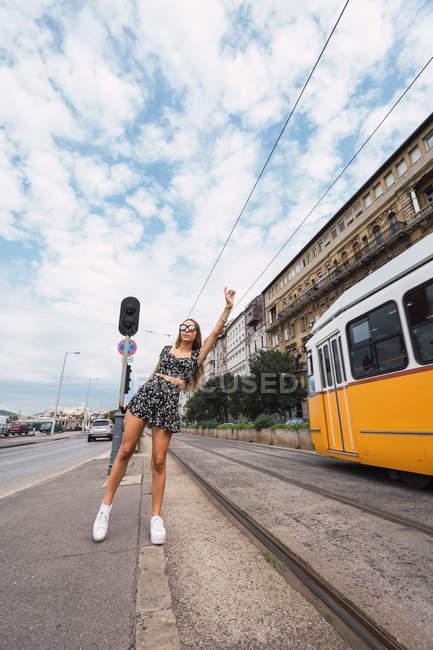 Donna magra attiva che alza la mano mentre aspetta il tram nelle vicinanze della ferrovia in pieno giorno nuvoloso a Budapest — Foto stock