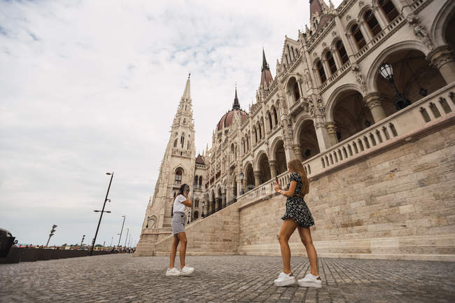 Side view of active touristic women taking pictures of each other on background of ancient building in Budapest — Stock Photo