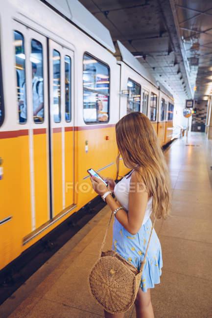 Seitenansicht der stilvollen Frau mit langen Haaren surft Handy und wartet vor der U-Bahn in der U-Bahn in Budapest — Stockfoto