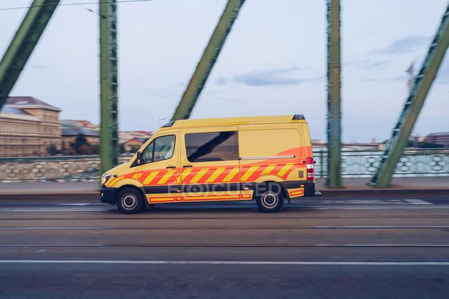 Вид сбоку желтого компактного фургона, быстро двигающегося по пустой дороге вдоль металлического моста в Будапеште — стоковое фото