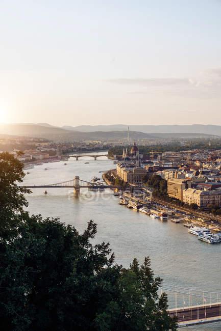Bateaux sur le canal de la ville coulant sous les ponts en plein jour à Budapest — Photo de stock