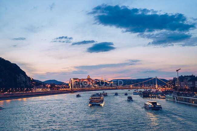 Bateaux sur la rivière calme reflétant le coucher de soleil coloré ciel et coulant sous un pont illuminé à Budapest — Photo de stock