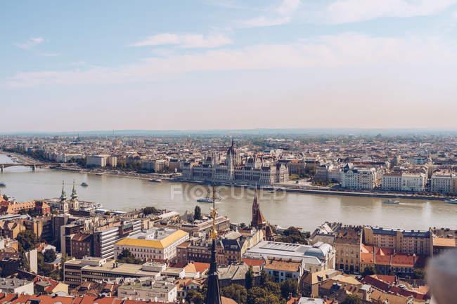 Bateaux sur la rivière calme reflétant ciel lumineux et coulant sous le pont le long de la ville densément peuplée Budapest — Photo de stock