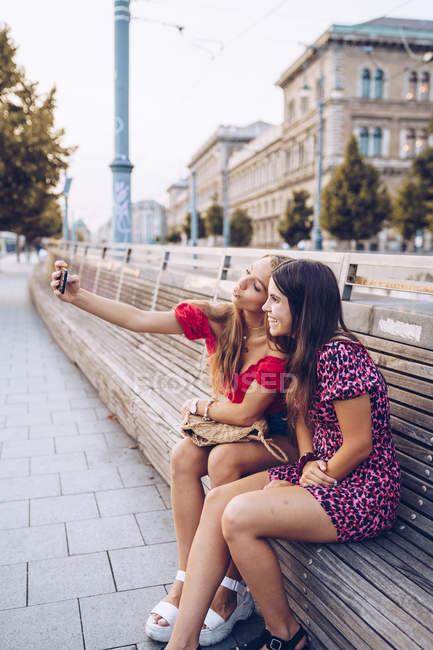 Le donne sorridenti attive in vestiti variopinti che prendono selfie su panchina lunga di legno su sfondo di edificio antico in Budapest — Foto stock