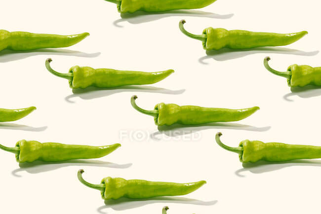 From above creative composition of sliced green whole pepper on white surface — Stock Photo