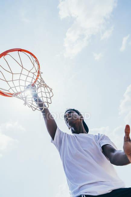 Мощный и энергичный афроамериканский спортсмен, висящий на баскетбольном круге после забивания мяча в сетке на детской площадке — стоковое фото